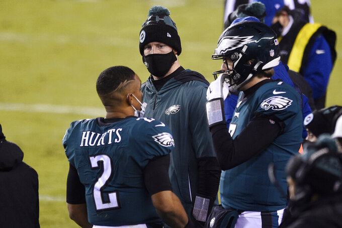Philadelphia Eagles' Jalen Hurts, from left, Carson Wentz and Nate Sudfeld talk during the second half of an NFL football game against the Washington Football Team, Sunday, Jan. 3, 2021, in Philadelphia. (AP Photo/Derik Hamilton)