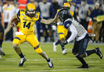 FILE - In this Friday, Dec. 20, 2019 file photo, Kent State quarterback Dustin Crum (14) carries the ball as Utah State safety Troy Lefeged Jr. (3) defends during the first half of the Frisco Bowl NCAA college football game in Frisco, Texas. (Kent State and star quarterback Dustin Crum are favored in the East Division. (AP Photo/Brandon Wade, File)