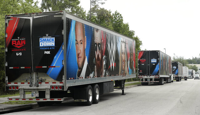 Equipment trailers are lined up at the entrance road to the WWE Performance Center Tuesday, April 14, 2020, in Orlando, Fla.  Florida's top emergency official last week amended Gov. Ron DeSantis' stay-at-home order to include employees at the professional sports and media production with a national audience, if the location is closed to the public. (AP Photo/John Raoux)
