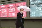 A man walks by an electronic stock board of a securities firm showing Japan's Nikkei 225 index in Tokyo, Wednesday, Nov. 25, 2020. Asian shares rose Wednesday after the Dow Jones Industrial Average closed above 30,000 points for the first time despite an ongoing pandemic, as progress in development of coronavirus vaccines kept investors in a buying mood. (AP Photo/Koji Sasahara)
