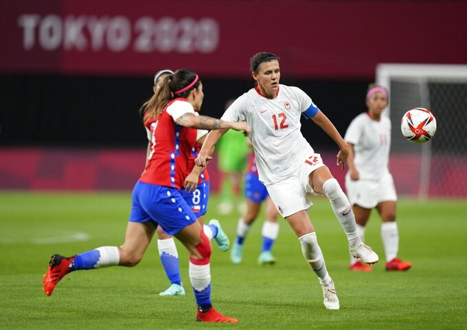 Chile's Carla Guerrero, left, and Canada's Christine Sinclair fight for the ball during a women's soccer match at the 2020 Summer Olympics, Saturday, July 24, 2021, in Sapporo, Japan. (AP Photo/Silvia Izquierdo)