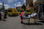 An emergency worker wearing a face mask transports an elderly patient to an ambulance at the 12 Octubre hospital in Madrid, Spain, Spain, Thursday April 30, 2020 as the lockdown to combat the spread of coronavirus continues. (AP Photo/Manu Fernandez)