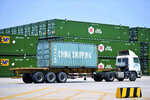 In this July 6, 2018, photo, a truck moves a China Shipping shipping container at a port in Qingdao in eastern China's Shandong Province. China's government on Wednesday, July 11, 2018, has criticized the latest U.S. threat of a tariff hike as