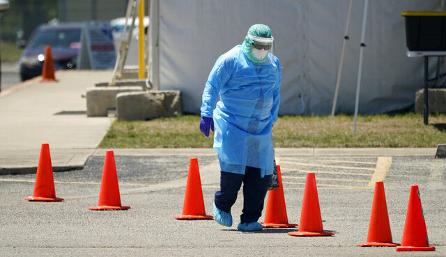 Medical personnel prepare a drive-thru COVID-19 testing site, Friday, Aug. 14, 2020, in San Antonio. Coronavirus testing in Texas has dropped significantly, mirroring nationwide trends, just as schools reopen and football teams charge ahead with plans to play. (AP Photo/Eric Gay)
