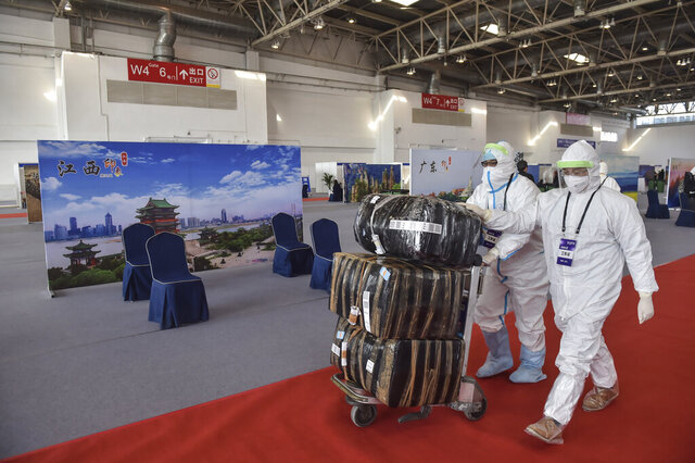 In this March 17, 2020 photo released by China's Xinhua News Agency, workers in protective suits push a cart with passengers' luggage at the New China International Exhibition Center, which has been converted into a facility to screen international flight passengers arriving in Beijing. As the pandemic expanded its reach, China and South Korea were trying to hold their hard-fought gains. China is quarantining new arrivals, who in recent days have accounted for an increasing number of cases, and South Korea starting Thursday will increase screenings of all overseas arrivals. The virus causes only mild or moderate symptoms, such as fever and cough, for most people, but severe illness is more likely in the elderly and people with existing health problems. (Peng Ziyang/Xinhua via AP)