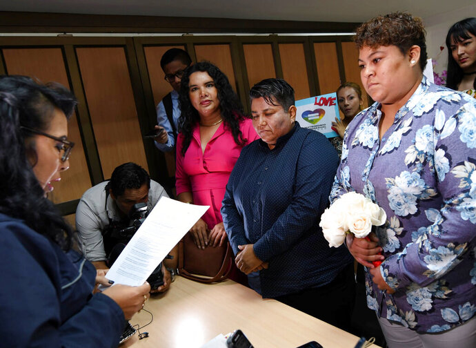 Michelle Aviles, right, and her partner Alexandra Chavez, center, get married at the Civil Registry in Guayaquil, Ecuador, Thursday, July 18, 2019. The same-sex couple became the first gay couple to marry in Ecuador after a recent decision by the Constitutional Court. (AP Photo)