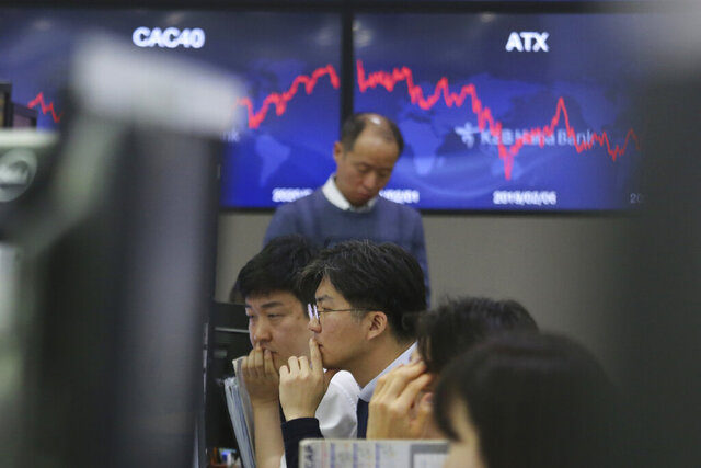 Currency traders watch monitors at the foreign exchange dealing room of the KEB Hana Bank headquarters in Seoul, South Korea, Wednesday, Feb. 5, 2020. Asian shares rose Wednesday on optimism that China's latest actions may help curtail some of the expected economic damage from the virus outbreak. (AP Photo/Ahn Young-joon)
