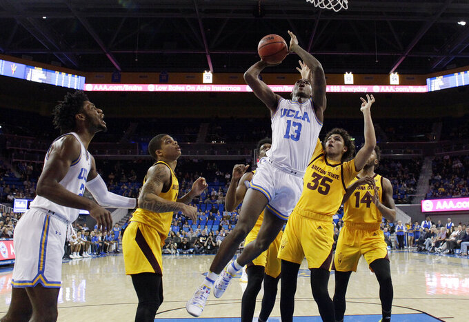 UCLA guard Kris Wilkes (13) drives past Arizona State forward Taeshon Cherry (35) during the first half of an NCAA college basketball game Thursday, Jan. 24, 2019, in Los Angeles. (AP Photo/Marcio Jose Sanchez)