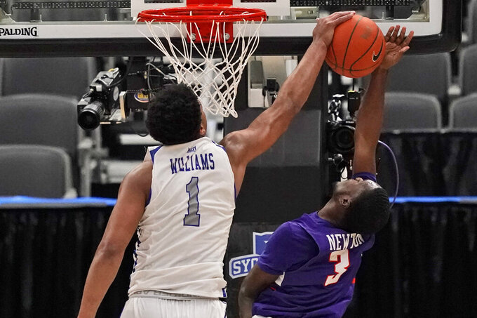 Indiana State's Tre Williams (1) blocks a shot by Evansville's Jawaun Newton (3) during the second half of an NCAA college basketball game in the quarterfinal round of the Missouri Valley Conference men's tournament Friday, March 5, 2021, in St. Louis. (AP Photo/Jeff Roberson)