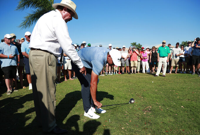 FILE - In this March 2, 2019, file photo, Brooks Koepka, center, takes a drop from out of bounds on the 12th hole as PGA rules official Slugger White, left, looks on during the third round of the Honda Classic golf tournament, Saturday, in Palm Beach Gardens, Fla. Russell is retiring after 40 years as a tour rules official. (AP Photo/Wilfredo Lee, File)