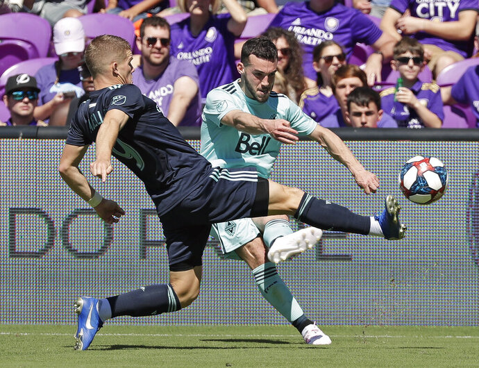 Orlando City's Chris Mueller, left, clears the ball away from Vancouver Whitecaps' Russell Teibert during the first half of an MLS soccer match, Saturday, April 20, 2019, in Orlando, Fla. (AP Photo/John Raoux)
