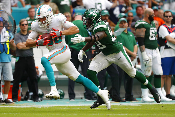 Miami Dolphins tight end Mike Gesicki (88) runs the ball against New York Jets outside linebacker James Burgess (58) during the first half of an NFL football game, Sunday, Nov. 3, 2019, in Miami Gardens, Fla. (AP Photo/Wilfredo Lee)