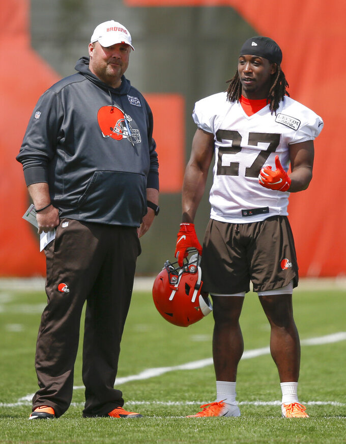 "FILE - In this May 15, 2019, file photo, Cleveland Browns' Kareem Hunt (27) talks with head coach Freddie Kitchens during an NFL football organized team activity session at the team's training facility in Berea, Ohio. Kitchens has been watching Kareem Hunt work toward redemption. On Sunday, May 19, Kitchens showed the running back that he's got his full support. Kitchens and general manager John Dorsey surprised Hunt by attending his baptism at True Vine Missionary Baptist Church on Cleveland's east side. Hunt, who has been suspended eight games by the NFL for two physical altercations, including one in which he shoved and kicked a woman, said last week he wanted ""to feel reborn.""(AP Photo/Ron Schwane, File)"