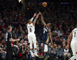 Portland Trail Blazers guard Damian Lillard shoots over New Orleans Pelicans guard Rajon Rondo during the first half in Game 1 of an NBA basketball first-round playoff series Saturday, April 14, 2018, in Portland, Ore. (AP Photo/Randy L. Rasmussen)