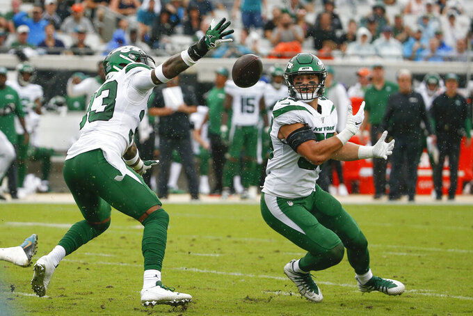 New York Jets strong safety Jamal Adams, left, and linebacker Blake Cashman go after a Jacksonville Jaguars tipped pass but cannot make the interception during the first half of an NFL football game, Sunday, Oct. 27, 2019, in Jacksonville, Fla. (AP Photo/Stephen B. Morton)