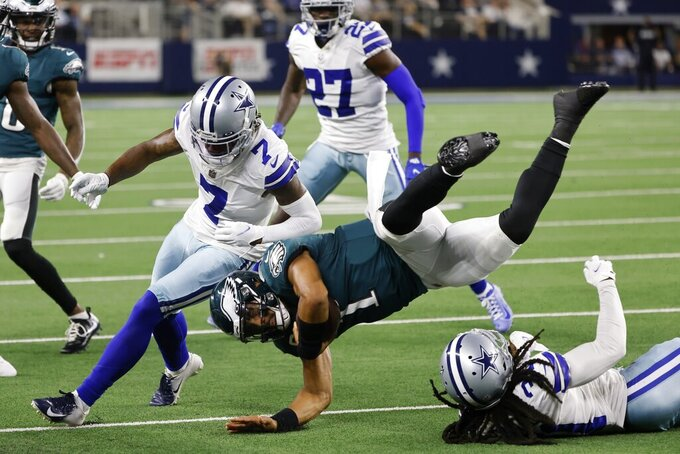 Dallas Cowboys' Trevon Diggs (7) and Maurice Canady, right, combine to stop Philadelphia Eagles quarterback Jalen Hurts, center, in the first half of an NFL football game in Arlington, Texas, Monday, Sept. 27, 2021. (AP Photo/Michael Ainsworth)