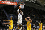 Villanova's Saddiq Bey, center, goes up for a dunk between La Salle's Scott Spencer, left, and Ed Croswell during the second half of an NCAA college basketball game, Sunday, Dec. 1, 2019, in Villanova, Pa. (AP Photo/Matt Slocum)