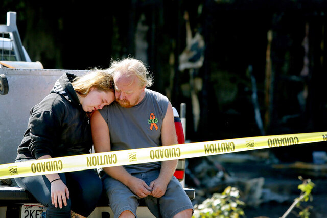 Kelsey Detter, left, embraces her father James Detter outside the scene of a fire in De Soto, Mo., on Sunday, Oct. 11, 2020. Four people killed in an eastern Missouri house fire included a married couple, their daughter and a granddaughter, the victims' family members said. Those killed in the early Sunday fire were Joe Detter, 76, and his wife, Frances Detter, 74, as well as their 37-year-old daughter Sherri Detter and 18-year-old granddaughter Kari Detter, the St. Louis Post-Dispatch reported.(Christine Tannous/ St. Louis Post-Dispatch via AP)