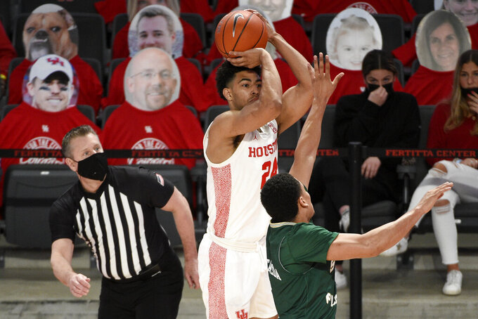Houston guard Quentin Grimes, center, shoots a three-point basket as South Florida guard Xavier Castaneda defends during the first half of an NCAA college basketball game, Sunday, Feb. 28, 2021, in Houston. (AP Photo/Eric Christian Smith)