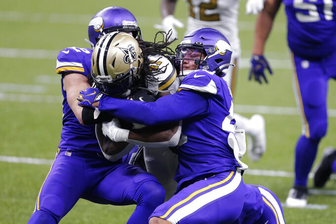 REMOVES REFERENCE TO TOUCHDOWN, WHICH HAPPENED ON SUBSEQUENT PLAY - New Orleans Saints running back Alvin Kamara (41) carries against Minnesota Vikings strong safety Harrison Smith, left, and linebacker Blake Lynch during the second half of an NFL football game in New Orleans, Friday, Dec. 25, 2020. (AP Photo/Brett Duke)