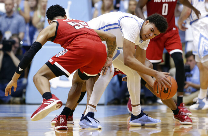 North Carolina's Cameron Johnson, right, controls the ball against North Carolina State's Blake Harris, left, during the second half of an NCAA college basketball game in Chapel Hill, N.C., Tuesday, Feb. 5, 2019. North Carolina won 113-96. (AP Photo/Gerry Broome)