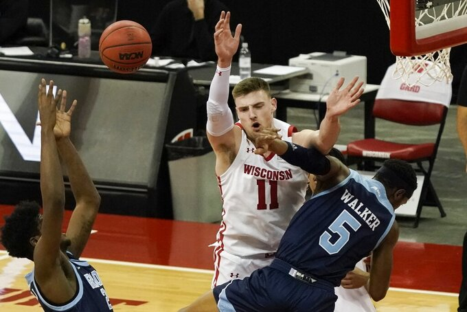 Rhode Island's Antwan Walker fouls Wisconsin's Micah Potter during the second half of an NCAA college basketball game Wednesday, Dec. 9, 2020, in Madison, Wis. (AP Photo/Morry Gash)