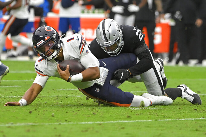 Las Vegas Raiders safety Johnathan Abram (24) tackles Chicago Bears quarterback Justin Fields (1) during the first half of an NFL football game, Sunday, Oct. 10, 2021, in Las Vegas. (AP Photo/David Becker)
