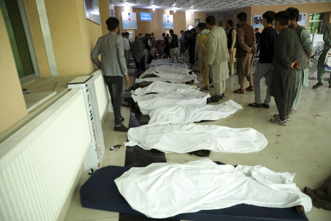 FILE - In this May 8, 2021 file photo, Afghan men try to identify bodies at a hospital after a deadly bomb explosion near a school west of Kabul, Afghanistan. In an interview with The Associated Press Thursday, July 22, 2021, Suhail Shaheen, Afghan Taliban spokesman and a member of the Taliban negotiation team, said the insurgent movement does not want to monopolize power, but there won't be peace until there is a new, negotiated government in Kabul and Afghan President Ashraf Ghani is removed. Shaheen said women will be allowed to work, go to school, and participate in politics but will have to wear the hijab, or headscarf. (AP Photo/Rahmat Gul, File)