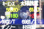 A man is reflected on the electronic board of a securities firm in Tokyo, Wednesday, Jan. 20, 2021. Asian shares were mostly higher Wednesday, ahead of Joe Biden's inauguration as president, ending President Donald Trump's four-year term. (AP Photo/Koji Sasahara)