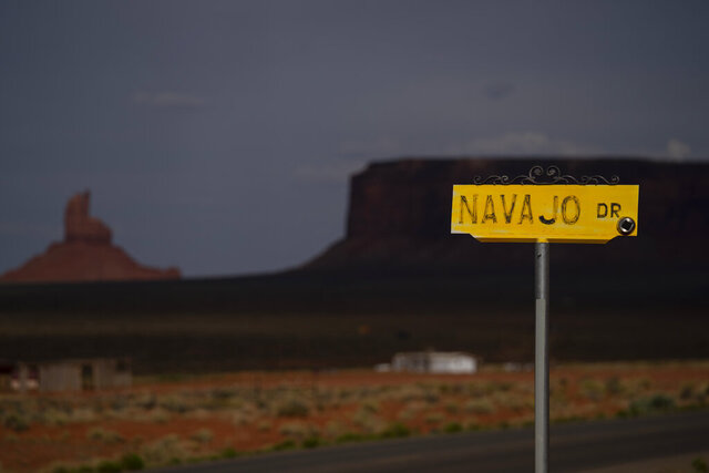 FILE - In this April 30, 2020, file photo, a sign for Navajo Drive is seen against a cloud-darkened Sentinel Mesa in Oljato-Monument Valley, Utah on the Navajo Reservation. Medical professionals serving the Navajo Nation made an urgent plea to residents Thursday, Dec. 3, 2020, to stay home as coronavirus cases rise. (AP Photo/Carolyn Kaster, File)