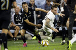 Sporting Kansas City defender Luis Martins, left, and Colorado Rapids midfielder Sam Nicholson chase the ball during the first half of an MLS soccer match, Saturday, Sept. 21, 2019, in Kansas City, Kan. (AP Photo/Charlie Riedel)