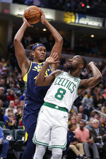 Indiana Pacers center Myles Turner (33) grabs a rebound over Boston Celtics guard Kemba Walker (8) during the first half of an NBA basketball game in Indianapolis, Wednesday, Dec. 11, 2019. (AP Photo/Michael Conroy)