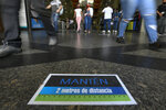 Customers walk by a sign on the ground reading in Spanish,