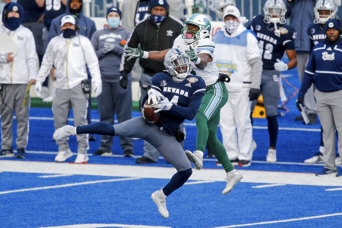Nevada defensive back EJ Muhammad (4) intercepts a pass intended for Tulane wide receiver Jha'Quan Jackson during the second half of the Famous Idaho Potato Bowl NCAA college football game Tuesday, Dec. 22, 2020, in Boise, Idaho. Nevada won 38-27. (AP Photo/Steve Conner)