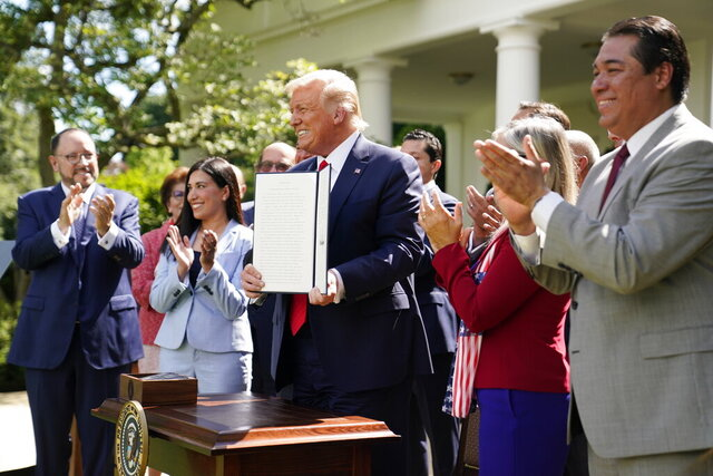 President Donald Trump holds an executive order on the