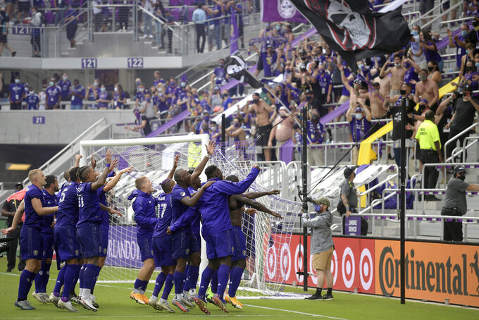 FILE - In this Nov. 21, 2020, file photo, Orlando City players celebrate in front of fans after defeating New York City FC on penalty kicks in an MLS soccer playoff match in Orlando, Fla. The owners of the Minnesota Vikings have finalized the acquisition of Orlando City, giving the Wilf family control of the MLS franchise.  (AP Photo/Phelan M. Ebenhack, File)