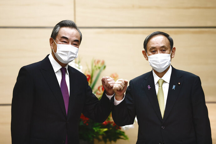 Japan's Prime Minister Yoshihide Suga, right, bumps elbows with China's Foreign Minister Wang Yi at the start of their meeting in Tokyo, Wednesday, Nov. 25, 2020. (Behrouz Mehri/Pool Photo via AP)