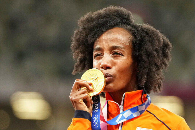 Gold medalist Sifan Hassan, of Netherlands, kisses her medal during the medal ceremony for the women's 10,000-meters at the 2020 Summer Olympics, Saturday, Aug. 7, 2021, in Tokyo. (AP Photo/Martin Meissner)