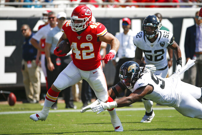 Kansas City Chiefs running back Anthony Sherman (42) runs past Jacksonville Jaguars defensive end Dawuane Smoot, lower right, and linebacker Najee Goode (52) during the first half of an NFL football game Sunday, Sept. 8, 2019, in Jacksonville, Fla. (AP Photo/Stephen B. Morton)