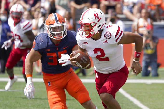 Nebraska quarterback Adrian Martinez scrambles away from Illinois linebacker Jake Hansen during the first half of an NCAA college football game Saturday, Aug. 28, 2021, in Champaign , Ill. (AP Photo/Charles Rex Arbogast)