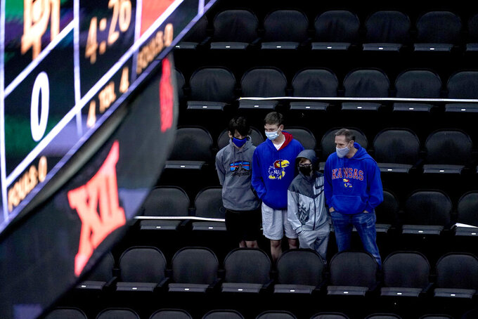 Kansas fans wait for an NCAA college basketball game between Baylor and Oklahoma State in the semifinals of the Big 12 tournament in Kansas City, Mo., Friday, March 12, 2021. Kansas had to drop out of their semifinal game against Texas because of a positive COVID-19 test on the team. (AP Photo/Charlie Riedel)