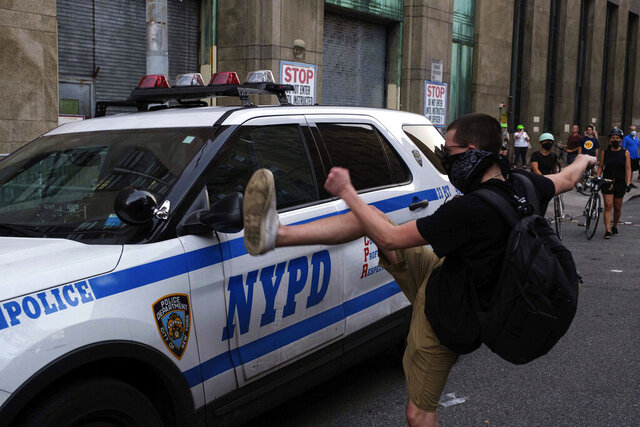 A protester kicks a police vehicle in an attempt to break its side mirror during a