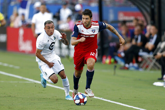 FILE - In this Aug. 10, 2019, file photo, FC Dallas defender Ryan Hollingshead plays the ball while Minnesota United forward Miguel Ibarra chases him during the first half of an MLS soccer match in Frisco, Texas. Hollingshead has been sheltering in place since Major League Soccer suspended the season because of the coronavirus outbreak. But his experience has been a bit different than other athletes in the same situation. He and his family have spent the time bonding with their foster son.  (AP Photo/Roger Steinman, File)