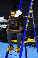 Baylor guard Davion Mitchell (45) sits with the trophy after the championship game against Gonzaga in the men's Final Four NCAA college basketball tournament, Monday, April 5, 2021, at Lucas Oil Stadium in Indianapolis. Baylor won 86-70. (AP Photo/Michael Conroy)