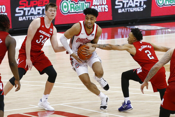 Ohio State's Justice Sueing, center, drives to the basket between Nebraska's Thorir Thorbjarnarson, left, and Trey McGowens during the second half of an NCAA college basketball game Wednesday, Dec. 30, 2020, in Columbus, Ohio. (AP Photo/Jay LaPrete)