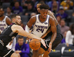 Sacramento Kings guard Buddy Hield, center, steals a pass intended for Melbourne United guard Chris Goulding, left, during the second half of an NBA exhibition basketball game in Sacramento, Calif., Wednesday, Oct. 16, 2019. The Kings won 124-110. (AP Photo/Rich Pedroncelli)