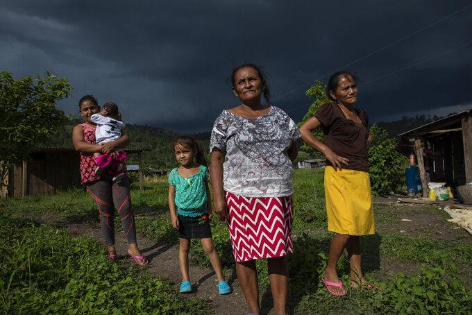 Residents gather for a community meeting under threatening skies in Hacienda Uno, Honduras, Friday, June 25, 2021, near El Espiritu, an area historically controlled by the Valle family drug traffickers. (AP Photo/Rodrigo Abd)