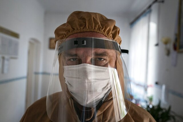 In this photo taken on Friday, May 1, 2020, doctor Ivan Venzhynovych, wearing special suit to protect against coronavirus, poses for a photo after morning examination patients with coronavirus at a hospital in Pochaiv, Ukraine. Ukraine's troubled health care system has been overwhelmed by COVID-19, even though it has reported a relatively low number of cases. (AP Photo/Evgeniy Maloletka)