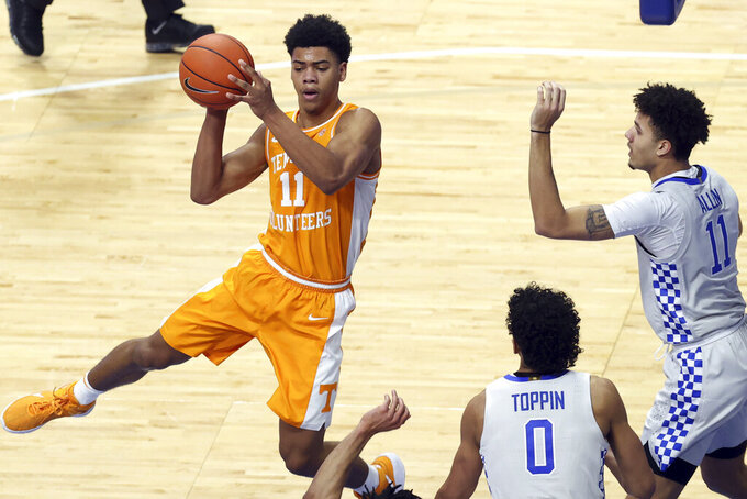 Tennessee's Jaden Springer, left, passes the ball away from Kentucky's Jacob Toppin (0) and Dontaie Allen during the first half of an NCAA college basketball game in Lexington, Ky., Saturday, Feb. 6, 2021. (AP Photo/James Crisp)