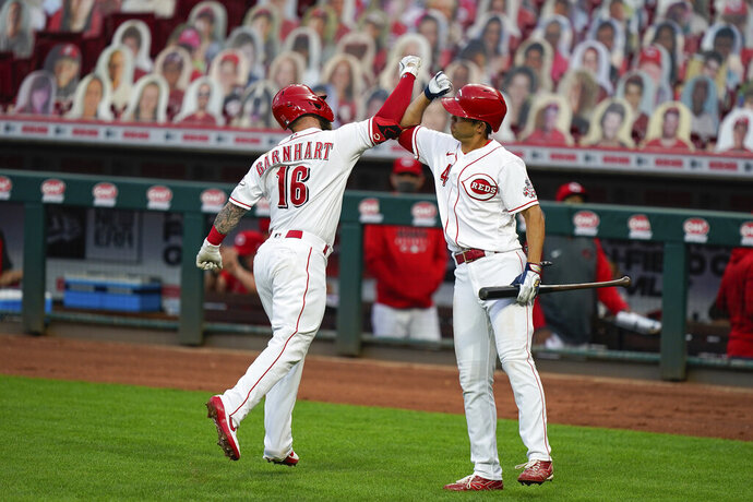 Cincinnati Reds' Tucker Barnhart (16) celebrates with Shogo Akiyama (4) after hitting a home run during the second inning of the team's baseball game against the Pittsburgh Pirates in Cincinnati, Tuesday, Sept. 15, 2020. (AP Photo/Bryan Woolston)
